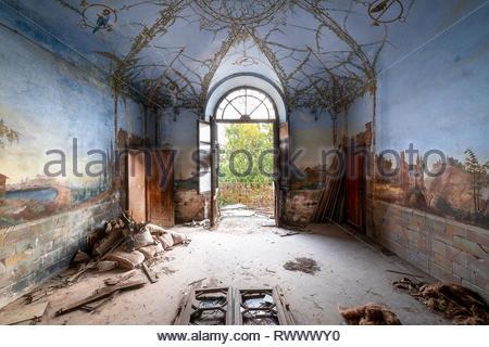 Une chambre dans une maison abandonnée avec une belle fresque couvrant à la fois les murs et le plafond. Banque D'Images