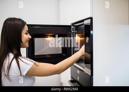 Belle jeune femme contrôler comment son gâteau est fait dans le four Banque D'Images