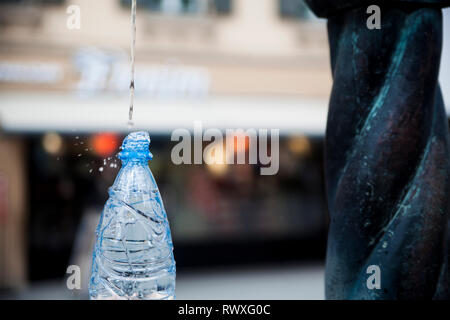 Verser de l'eau d'une fontaine publique de bouteille bleue. Dept peu profondes de champ. Banque D'Images