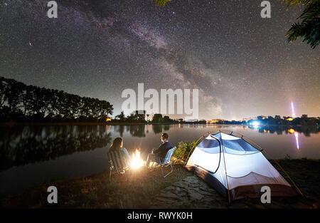 Nuit camping à bord du lac. Vue arrière de jeune famille - homme et femme assise sur des chaises près de camp et tente, bénéficiant soir ciel plein d'étoiles, calme surface de l'eau, les lumières de la ville, sur l'arrière-plan. Banque D'Images