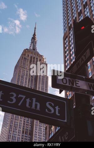 Low angle view de panneaux routiers contre l'Empire State Building en ville Banque D'Images