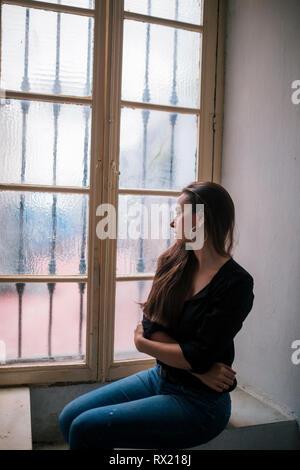 Femme avec les bras croisés à la fenêtre à travers tout en restant assis à la maison
