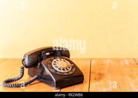 Rotatif rétro vieux téléphone noir placé sur une table en bois. Banque D'Images