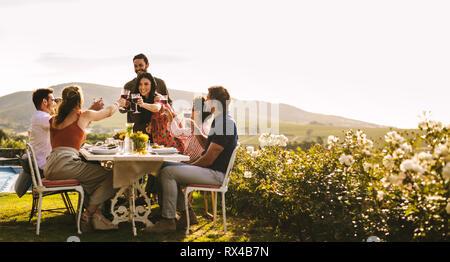 Porter un toast avec quelques amis assis à table au cours de partie. Groupe d'amis pour célébrer une occasion spéciale avec des boissons. Banque D'Images