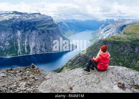 Girl in red jacket est assis sur un rocher et regarde montagnes près de Trolltunga. Attraction touristique populaire. - Lac Ringedalsvatnet dans la municipalité de Odda Banque D'Images