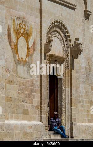 MATERA, ITALIE - 27 août 2018: paysage chaud jour d'été, la mendicité sans création d'homme avec le baseball hat repose sur l'église d'escalier de belle pierre sculptée