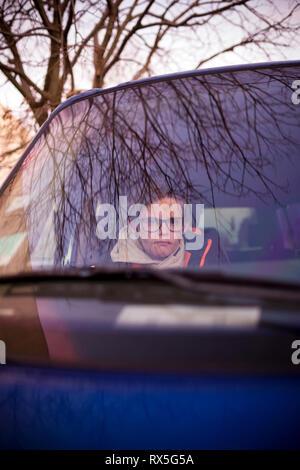 en regardant un garçon de 11 ans avec des verres assis en voiture à travers le pare-brise sur une course scolaire tôt le matin Banque D'Images