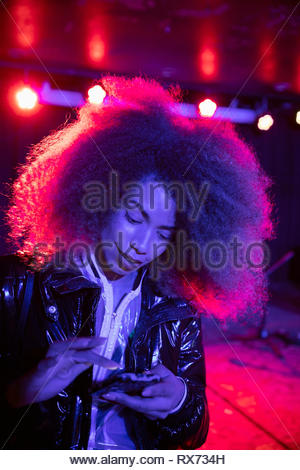 Young woman using smart phone in nightclub Banque D'Images