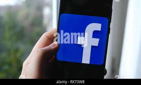 Utilisation de main et de doigts application facebook symbole sur un smartphone Banque D'Images