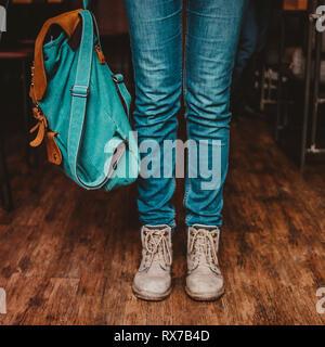 Rogner la photo de jeune femme pieds girl traveler en jeans et bottes à l'intérieur sac à dos