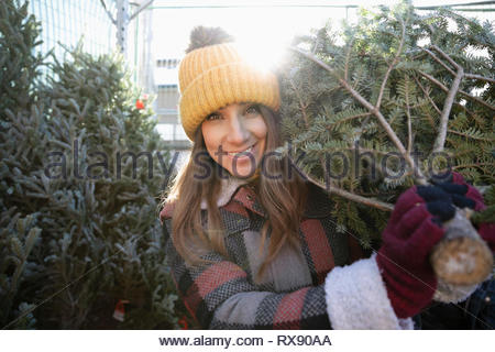 Portrait happy woman carrying Christmas Tree at Christmas market Banque D'Images