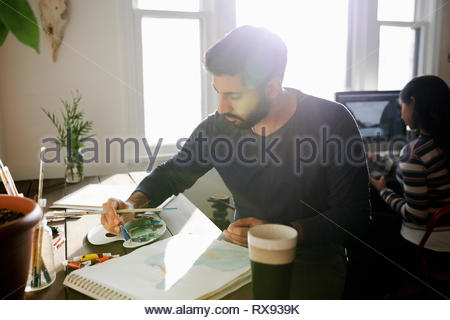 Artiste masculin porté painting the home office Banque D'Images