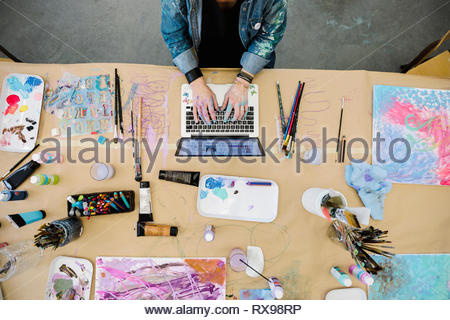 Vue de dessus l'artiste féminine à l'aide d'un coffre entouré de fournitures de peinture Banque D'Images