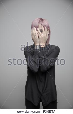 Magnifique Portrait de genre non-binaires personne aux cheveux roses se cacher derrière les mains Banque D'Images