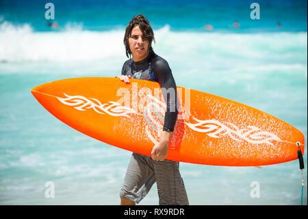 RIO DE JANEIRO - Février 9, 2017: un jeune surfeur brésilien se promène avec son surf à travers les vagues à l'Arpoador, spot de surf populaire. Banque D'Images