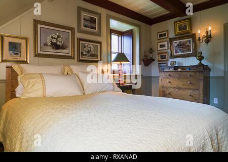 Chambre avec grand lit en bois antique, commode et tableaux encadrés dans la chambre principale à l'étage dans une ancienne circa 1805 style cottage Canadiana Banque D'Images