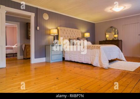 Lit queen size avec couvre-lit blanc, tête de lit en tissu beige, bleu clair des tables avec des tiroirs en merisier commode et restauré dans la chambre à coucher principale avec Banque D'Images
