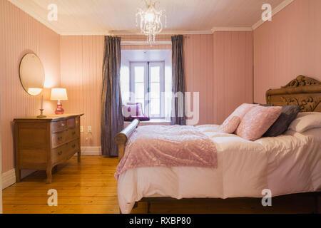 Trois-quart lit avec couvre-lit blanc et un lit en bois et le marchepied à l'aide de détails sculptés, commode dans la chambre d'amis avec pla couleur rose Banque D'Images