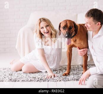 Jeune famille avec leur chien assis sur le lit dans la chambre à coucher Banque D'Images