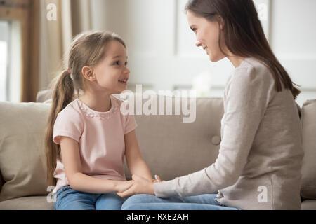 Mère et enfant tenant mains parler sitting on sofa