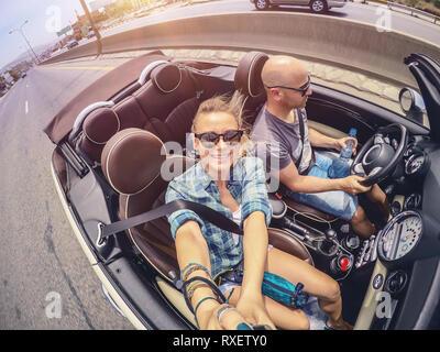Heureux couple ouvert de conduite automobile et la prise de miel en selfies, vacances auto convertible, compagnons d'âme profitant de road trip, profitant de l'été Banque D'Images