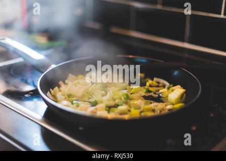Les poireaux et autres légumes sont cuits dans une poêle Banque D'Images
