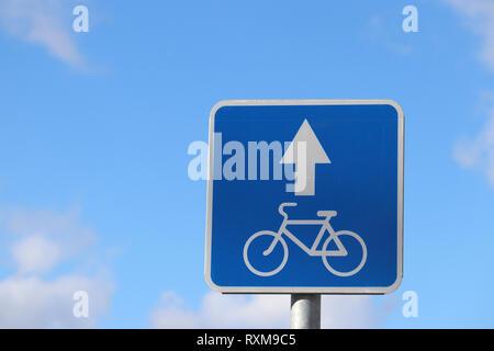 Location panneau routier isolé sur ciel bleu. Vélo blanc symbole sur le carré bleu avec la flèche, la voie cyclable