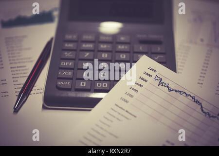 Lieu de travail avec les documents d'affaires, la croissance des graphiques, calculatrice et stylo Banque D'Images