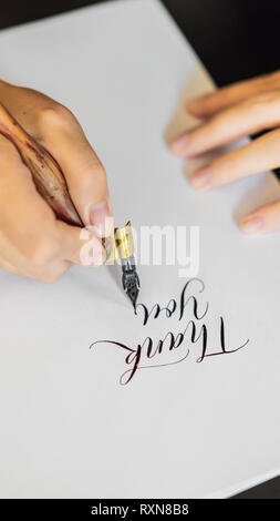 Calligraphe mains écrit une phrase sur du papier blanc. Expression - merci. L'inscription des lettres ornées d'ornement. Design graphique, calligraphie, lettrage Banque D'Images