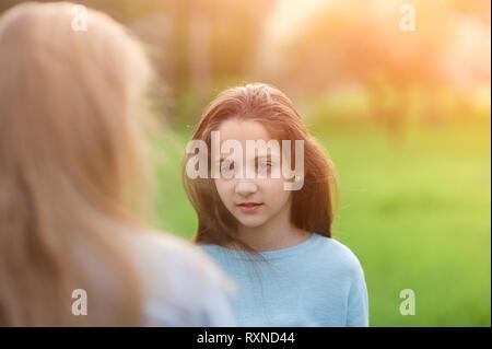 Belle petite caucasian girl with long hair regardant son amie avec intérêt à l'extérieur Banque D'Images