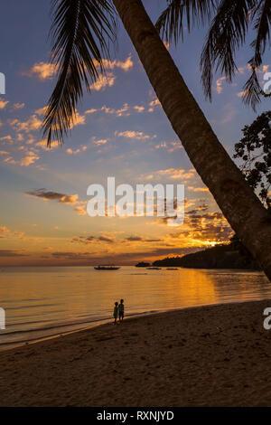 Coucher du soleil sur une plage avec des enfants qui jouent et l'homme silhouette, la mer à marée basse, une scène paisible dans une soirée d'ambiance de vacances