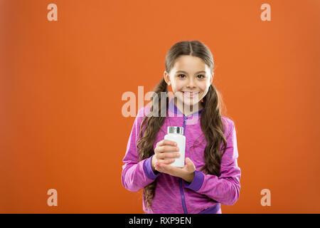 Pour une flore digestive. Complément alimentaire pour les enfants. Prendre des suppléments de vitamine. Maintenez la bouteille fille médicaments. La vitamine et medicine concept. Fille enfant prendre des médicaments. Besoin de suppléments vitaminiques. Banque D'Images