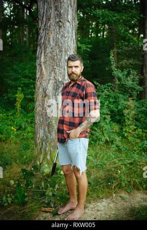 Hipster avec longue barbe sur le paysage verdoyant. Homme barbu avec pelle en forêt. Séjour touristique en chemise à carreaux et jean shorts barefoot voyage Banque D'Images