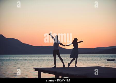 Couple dancing at beach sur journée ensoleillée dans le coucher du soleil. Banque D'Images