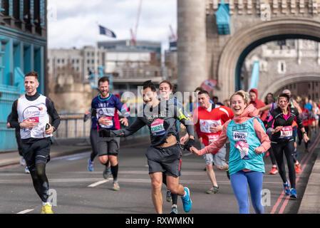 Ellie Hale s'exécutant dans la vitalité demi demi marathon traversant le Tower Bridge, Londres, Royaume-Uni. Le vent souffle fort porteur Banque D'Images