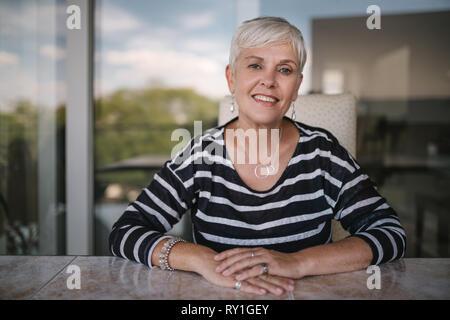 Belle femme âgée souriant à la caméra. Portrait of a young woman avec les mains croisées sur la table, à l'extérieur sur le balcon. Belle Banque D'Images