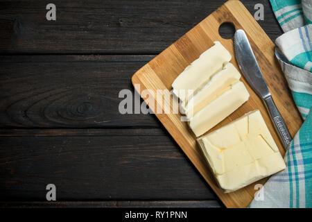 Beurre sur une planche de bois. Sur un fond de bois. Banque D'Images