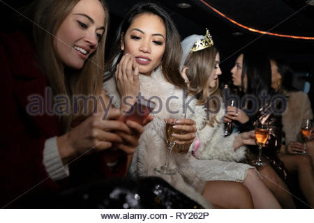 Et Bachelorette friends drinking champagne in limousine Banque D'Images
