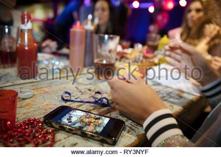 Femme avec smart phone manger à la fin de nuit diner avec des amis Banque D'Images