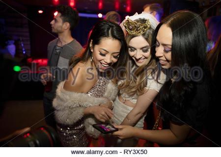 Bachelorette et amis à l'aide de smart phone in nightclub Banque D'Images