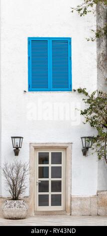 Une fenêtre avec des volets bleus et porte sur un mur blanc dans le style grec de la ville de Santorini sur une journée ensoleillée. Photo verticale Banque D'Images