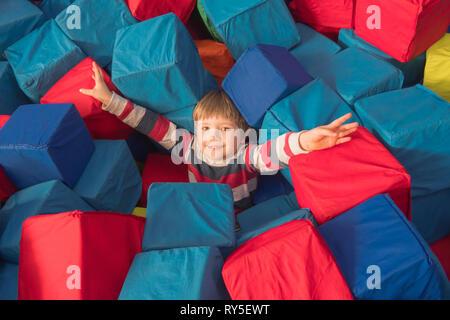 Garçon jouant avec des cubes dans la piscine à sec du jeu d'enfant pour l'anniversaire. centre de divertissement. jeu intérieur en mousse de caoutchouc dans la fosse Banque D'Images