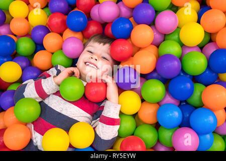Petit Garçon jouant dans la piscine avec des billes en plastique dans la pépinière. À l'intérieur des activités pour les enfants. Développement d'émotions positives background Banque D'Images
