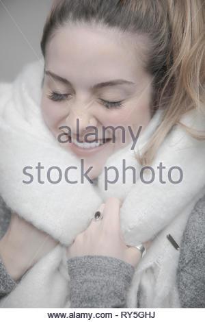 Carefree Portrait jeune blonde femme enveloppée dans couverture chaude Banque D'Images
