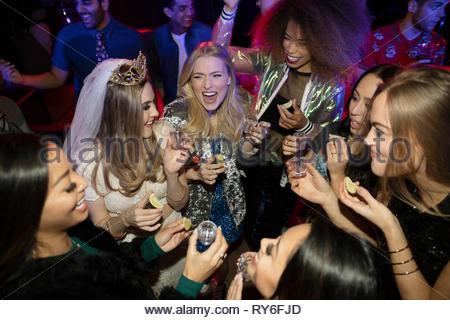 Et les amis de bachelorette de prendre des coups de tequila sur plancher de danse en discothèque Banque D'Images