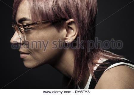 Beau portrait de profil de genre non-binaires personne aux cheveux roses et lunettes Banque D'Images