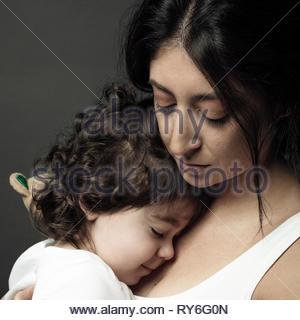 Serene Latina woman holding toddler fille Banque D'Images