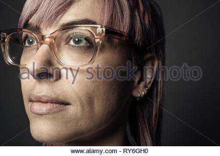 Close up portrait of certain beau sexe non-binaires personne aux cheveux roses et lunettes Banque D'Images