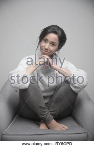 Portrait confiant belle jeune femme jamaïcaine en fauteuil Banque D'Images