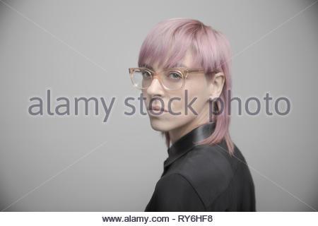 Portrait confiant belle personne de genre non-binaires aux cheveux roses et lunettes Banque D'Images